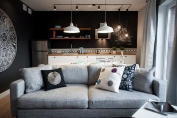 salon, czarna ściana z białym wzorem, jasno szara sofa, białe meble kuchenne