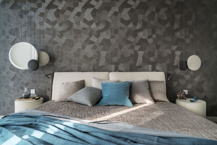apartament, nad łóżkiem wiszą lampy Cosmos marki Vibia. Na ścianie grafitowa tapeta