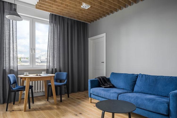 Salon z niebieską sofą, stolikiem kawowym i mały stolem jadalnianym dla dwóch osób