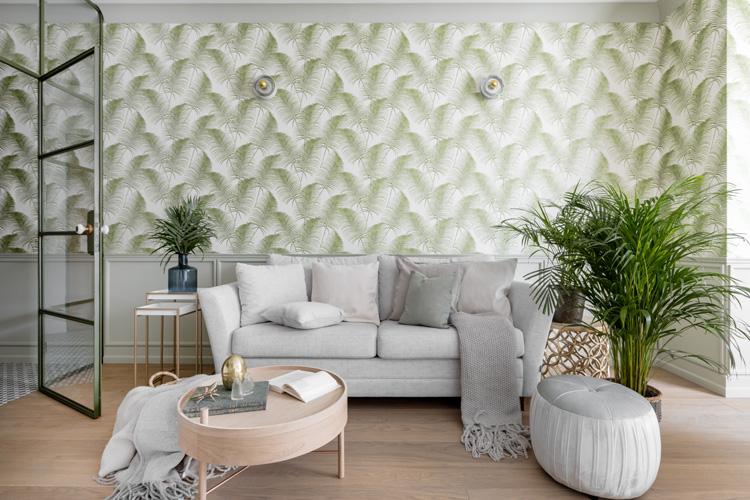 sofa na tle ściany z tapetą roślinną