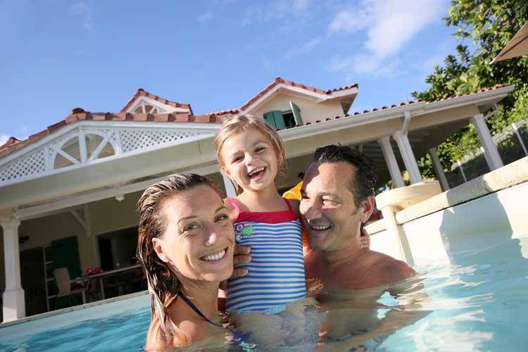 Szczęśliwa rodzina kąpie się w basenie przy domu.