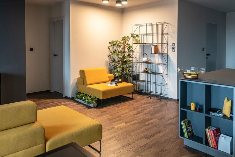 żółty tapicerowany wypoczynek w szarym apartamencie