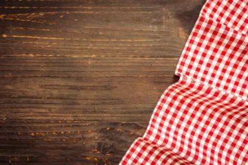 Stół widoczny z góry, a na nim kawałek obrusu w czerwono białą kratę
