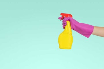 Osoba trzymająca butelkę z płynem do czyszczenia