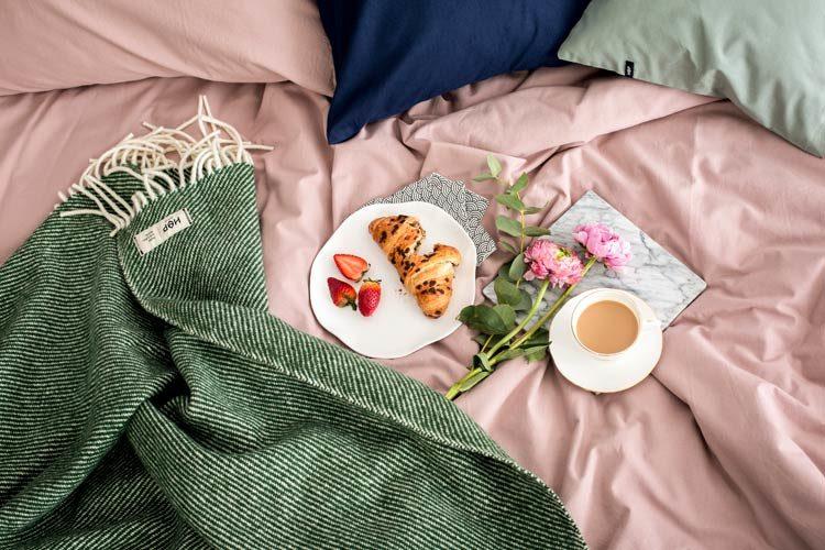 Kawa, croissant, kwiaty i zielony koc położony na łóżku z różową pościelą