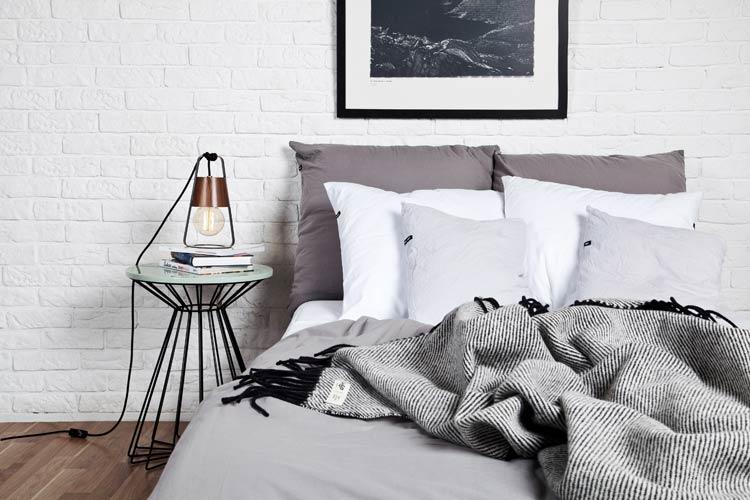 Sypialnia w szarościach, na łóżku leży szary pled