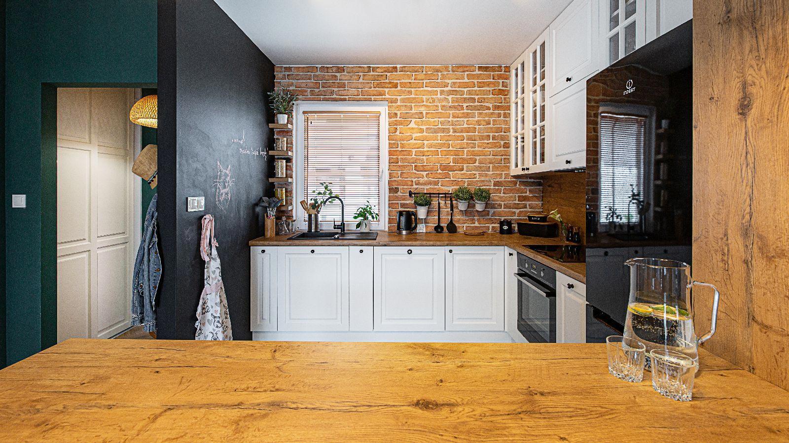 kuchnia z białymi frontami i blatem z naturalnego drewna. Ściana z cegły