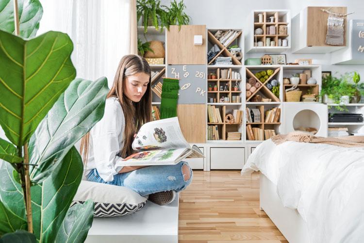 nastolatka w swoim pokoju czyta książkę