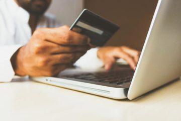 Mężczyzna opłaca kartą kredytową zakupy dokonane przez internet